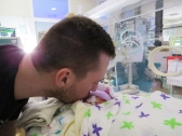 Daddy kisses NICU baby Silver Rose