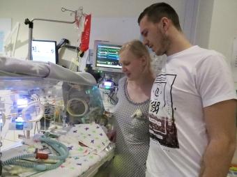 mum and dad bedside bonding NICU baby silver rose